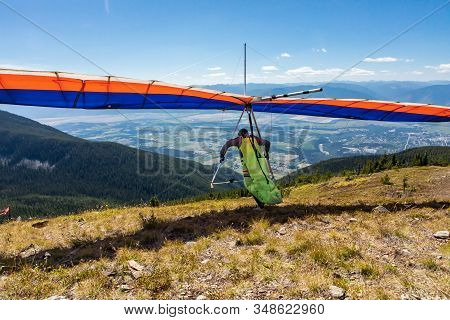 Hang Glider Pilot Running And Taking Off. Scenic View Over Kootenay Valley Mountains. View From Behi