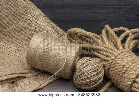 Jute Rope And Spools Of Burlap Threads Or Jute Twine In Close-up On Rustic Wooden Background