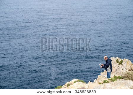 Sagres, Portugal - January 22, 2020: Tourist Man Gets Dangerously Close To The Edge Of The Cliff At