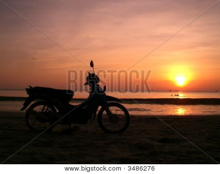 Motor Bicycle On The Sunset Beach