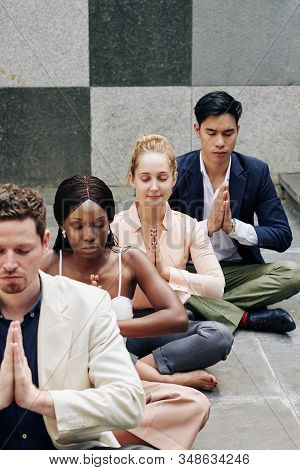 Group Of Concentrated Business People Closing Eyes When Meditating Outdoors
