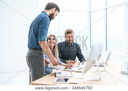 Business Team Discussing Working Documents In A Light Office.