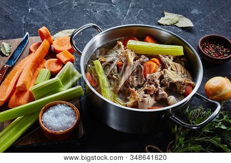 Cooked Chicken Stock With Vegetables And Aromatic Herbs In A Stockpot, Ingredients On A Kitchen Work