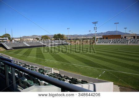 Football Field, Soccer Field, Baseball Field, Sports Field. Sports Arena. Outdoor Green Grass Sports Arena. Bleachers and Sports Space outdoors.