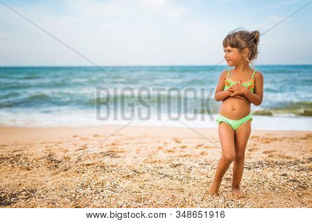 Joyful Little Girl Enjoys A Beach Day While Relaxing At Sea On A Sunny Warm Summer Day. Summer Vacat