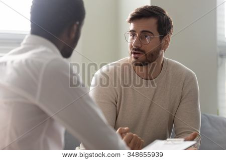 African Counsellor Sitting In Front Of Patient Listens His Complaints