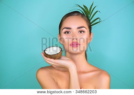 Beauty Woman with coconut Portrait. Spa model girl holding coco nut. Pretty young brunette woman face. Skin care. Youth. Treatment. Beautiful Fashion Model Girl Face. Perfect Skin. Health care