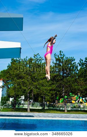 Little Caucasian Female 8 Years Old Girl Jumping From A Diving Platform.