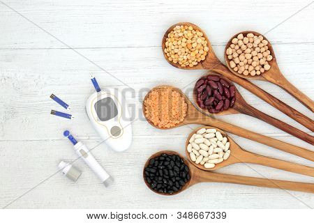 Low GI health food for diabetics with blood sugar testing monitor & lancing device with legumes in spoons high in vitamins, minerals, anthocyanins, antioxidants, smart carbs. Below 55 on the GI index.