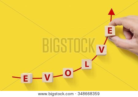 Wooded Cube Block On Yellow Background With Word Evolve And Copy Space For Your Text