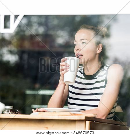 Young Caucasian Woman Sitting Alone In Coffee Shop Thoughtfully Leaning On Her Hand, Looking Trough