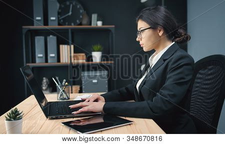 Successful Businesswoman In Classic Suit And Eyewear Working On Laptop Sitting At Desk In Office