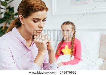 Worried Mother Sitting Near Diseased Daughter In Bed