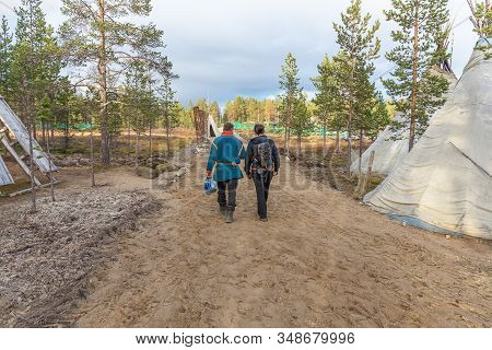 Woman Tourist Is Walking With Sami Man. Saami Village On The Kola Peninsula, Russia