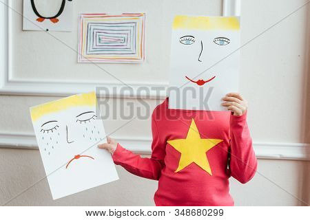 Kid Holding Two Paintings With Happy And Sad Faces