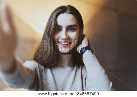 Young Model With Long Brown Hair Posing In Front Of Camera. Pretty Girl Taking Selfie For Publishing