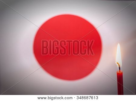 Burning Candle On The Background Of The Flag Of Japan. The Concept Of Mourning And Sorrow In The Cou