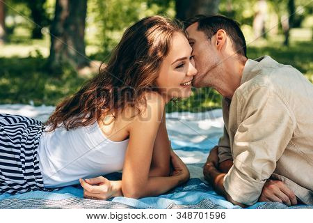 Adorable Couple In Love Dating Outdoors At The Park On A Sunny Day. Happy Couple In Love Embracing E