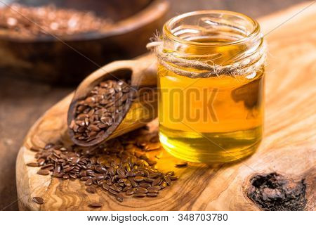 Flax Seeds Oil And Raw Seeds On Wooden Background. Flax Oil And Flax Nuts