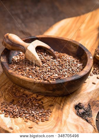 Flax Seeds Or Line  In Bowl  On Wooden Background. Flax Seeds And Oil In Glass Bottle