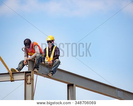 Two Builders Welding Steel On High-rise Steel Frame Without Safety Belt On Construction Site With Bl