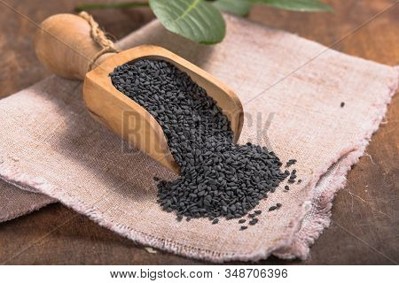 Black Sesame Seeds In The Wooden Spoon. Pile Of Scattered Black Sesame Seeds With A Wooden Spoon And