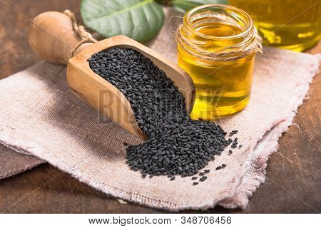 Black Sesame And Oil On Old Wooden Background. Black  Sesame Seeds And Oil Sesame