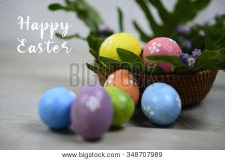 Easter Eggs On Easter Day. Happy Easter Text On Background Of Colorful Eggs On Wooden Rattan Basket.