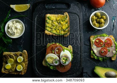 Grey Cutting Board With Sandwich With Tomato, Egg And Purple Onion And Avocado And Cheese Sandwich,