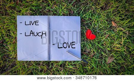 Inspirational Words Of Live Laugh Love Written On Notepaper With Nature Background