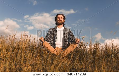 Adult Bearded Guy In Casual Clothes Sitting Crossed Legged In Meadow And Meditating With Closed Eyes