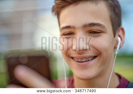 Smiling teenager  looks to the cell phone screen, in the city.  Close-up portrait of a smiling young man with smartphone, in the street.  Happy teenage boy is using phone, outdoors. Soft focus effect.