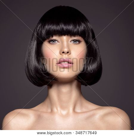 Woman with beauty short black hair - posing at studio. Fashion model with  straight hair. Fashion model at studio. Beautiful woman with a style  hairstyle. Closeup portrait of a fashion model.