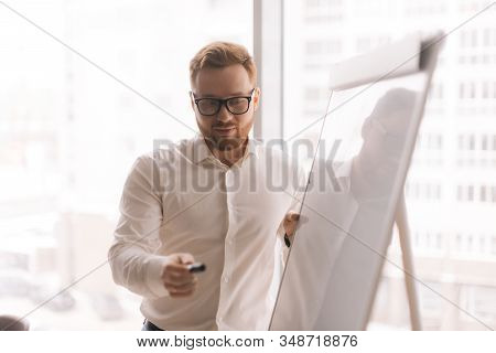 Close-up Portrait Of Young Team Leader With Glasses Giving Presentation To Colleagues On Whiteboard