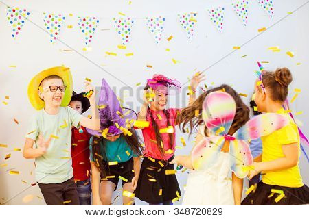 Excited Happy Children Dancing At Birthday Party. Kids Enjoying Glitter Confetti
