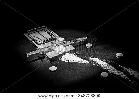 Addiction And Dependence On Drugs. A Stock Photo Of A Mousetrap With A Bait In The Form Of Various D