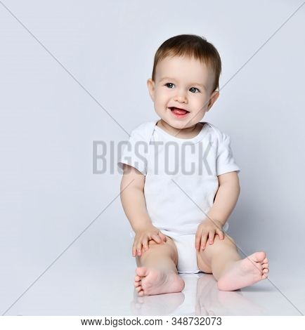 Happy Laughing Screaming Frolic Infant Baby Boy Toddler In White Bodysuit Is Sitting On The Floor Lo