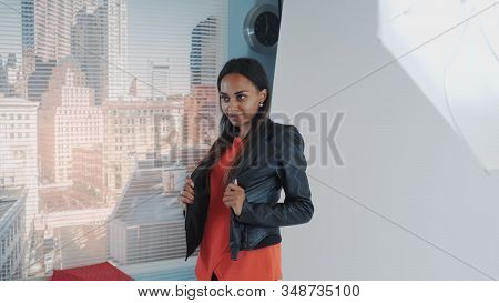 Close-up Of Female Assistant Helping African Model To Wear Jacket During Photo Session In Studio. Th