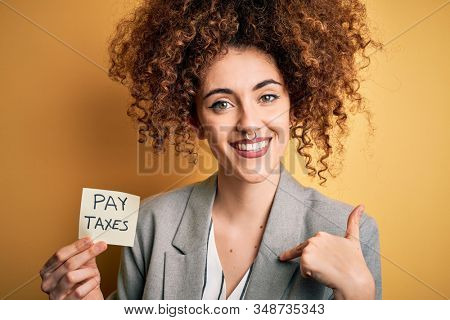 Young business woman with curly hair holding pay taxes to goverment reminder over yellow background with surprise face pointing finger to himself