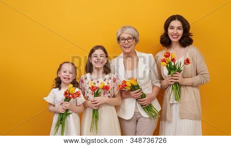 Happy women's day! Children daughters are congratulating mom and grandma giving them flowers tulips.Granny, mum and girls smiling on color yellow background. Family holiday and togetherness.