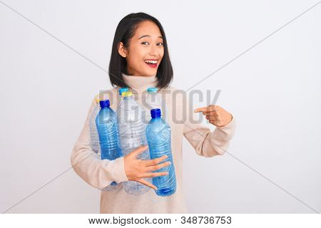 Young beautiful chinese woman recycling plastic bottles over isolated white background very happy pointing with hand and finger