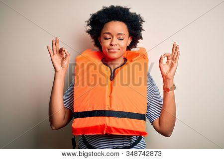 Young African American afro woman with curly hair wearing orange protection lifejacket relax and smiling with eyes closed doing meditation gesture with fingers. Yoga concept.