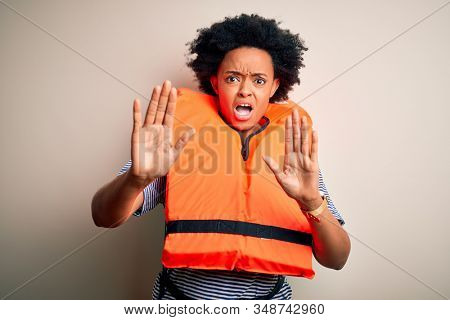Young African American afro woman with curly hair wearing orange protection lifejacket afraid and terrified with fear expression stop gesture with hands, shouting in shock. Panic concept.