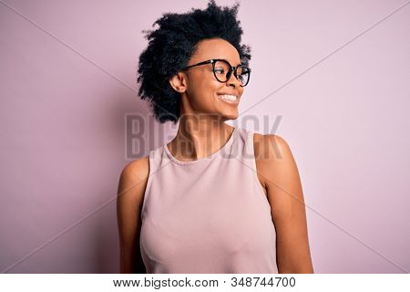 Young beautiful African American afro woman with curly hair wearing t-shirt and glasses looking away to side with smile on face, natural expression. Laughing confident.