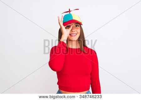 Young beautiful girl wearing fanny cap with propeller standing over isolated white background doing ok gesture with hand smiling, eye looking through fingers with happy face.