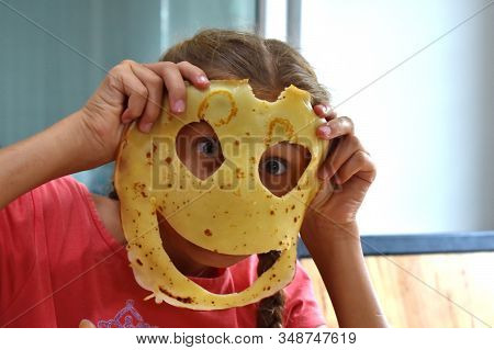 The Holes In The Pancake. Funny Round Pancake. The Girl Dabbles With Fried Pancake. The Child Eats T