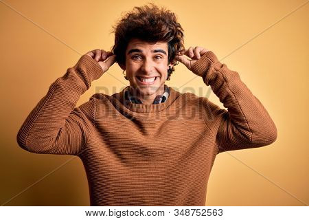 Young handsome man wearing casual shirt and sweater over isolated yellow background Smiling pulling ears with fingers, funny gesture. Audition problem