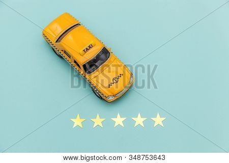 Yellow Toy Car Taxi Cab And 5 Stars Rating Isolated On Blue Background. Smartphone Application Of Ta