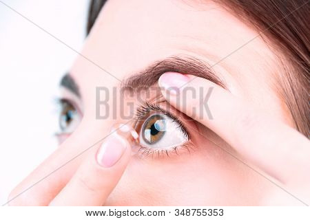Closeup Female Face, Finger Is Holding Soft Contact Lens. Woman Is Going To Insert Lenses. Tool For