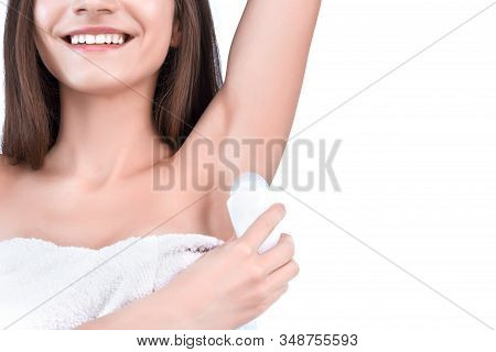 Closeup Of Female Hand Is Holding White Bottle With Deodorant For Eliminating Perspiration, Odors. Y